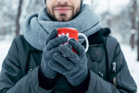 partial view of man holding cup of hot coffee in hands on winter day in park