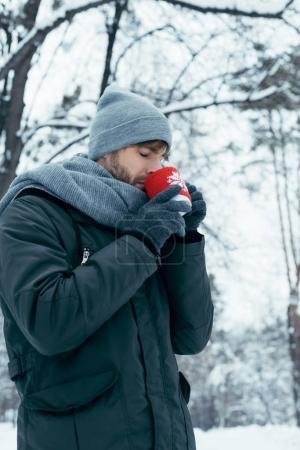young man holding cup of hot coffee in hands in winter park