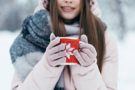 Photo for Selective focus of woman with cup of hot coffee in hands in snowy park - Royalty Free Image