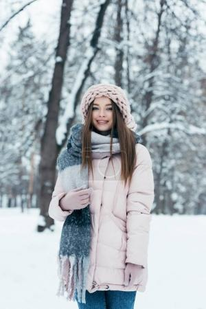 portrait of smiling woman in winter clothing looking at camera in snowy park