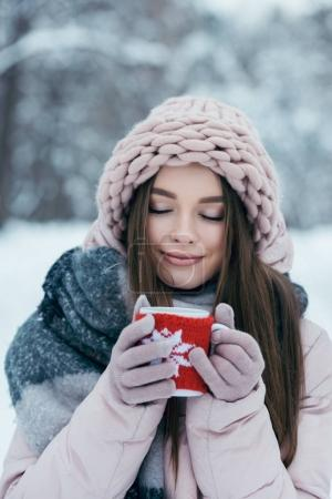 portrait of beautiful woman with eyes closed and cup of hot coffee in hands in snowy park