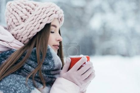 Photo for Side view of beautiful young woman with cup of hot coffee in hands and eyes closed in snowy park - Royalty Free Image