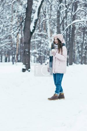 attractive woman in winter clothing with coffee to go on winter day in park