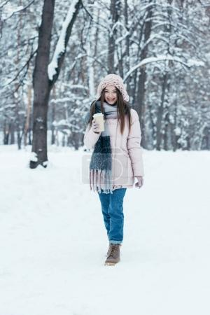 attractive woman in winter clothing with coffee to go on winter day walking in park