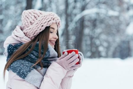 Photo for Side view of beautiful young woman with cup of hot coffee in hands in snowy park - Royalty Free Image