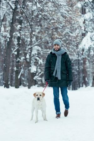 young man walking with dog on leash in winter park