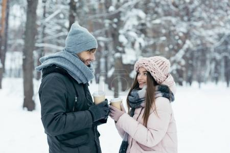 side view of cheerful couple with coffee to go in snowy park