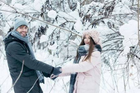 smiling couple holding hands and looking at camera in snowy forest