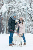 cheerful couple with coffee to go and dog on leash in snowy park