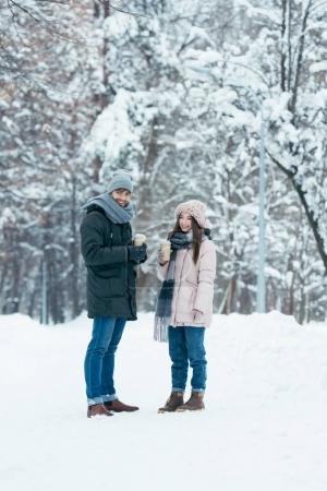 Photo for Cheerful couple with coffee to go standing in snowy park - Royalty Free Image