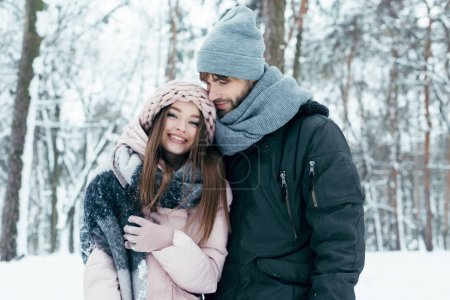 Photo for Young man hugging girlfriend in winter forest - Royalty Free Image