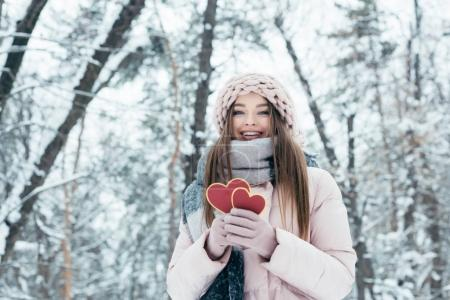 portrait of beautiful young woman with hearts in hands looking at camera in snowy park