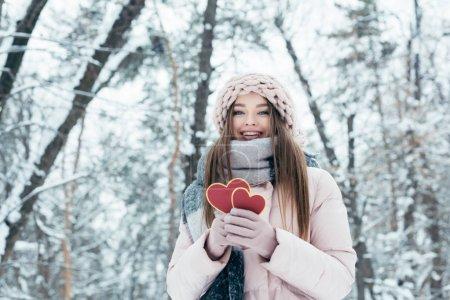 Photo pour Portrait de la belle jeune femme avec un cœur en mains regardant la caméra dans le parc enneigé - image libre de droit