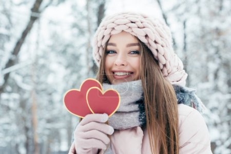 portrait of beautiful young woman with hearts in hand looking at camera in snowy park