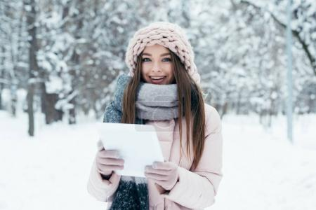 portrait of smiling young woman with tablet in winter park