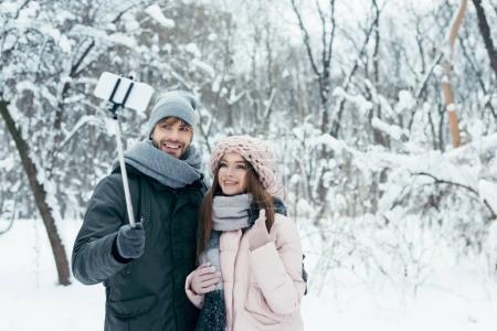 Photo pour Couple souriant confondus selfie sur smartphone à winter park - image libre de droit
