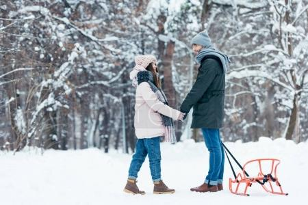 young couple holding hands and looking at each other in winter forest