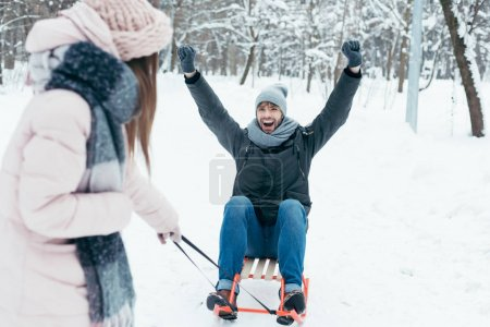 partial view of young couple sledging together on winter day in park