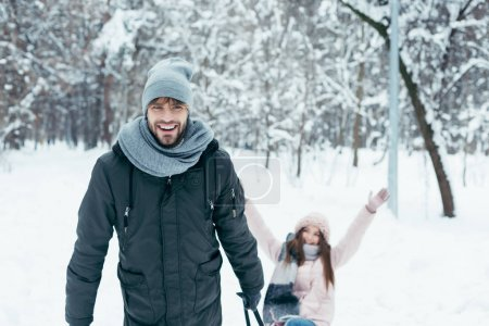 young couple sledging together on winter day in park