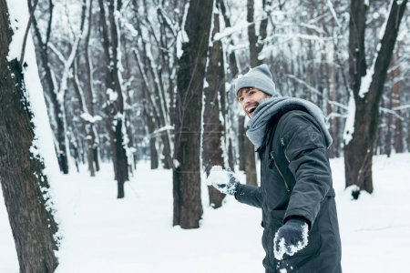 portrait of happy young man playing with snow in winter park