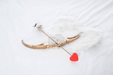 top view of wings, bow and arrow on white bed