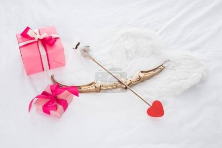 top view of presents, wings, bow and arrow on bed