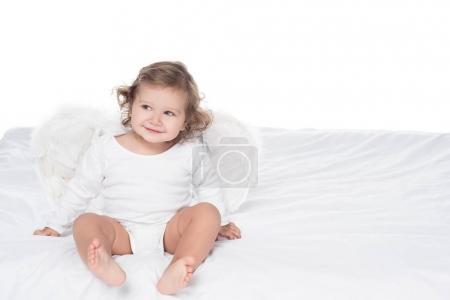 Photo pour Adorable bébé souriant avec des ailes assises sur le lit, isolé sur blanc - image libre de droit
