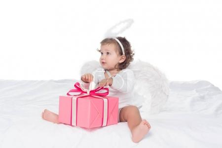 little angel with nimbus sitting on bed with gift boxes, isolated on white