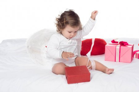 little angel sitting on bed with gift boxes, isolated on white