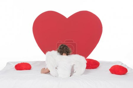 little cherub with wings lying on bed with hearts, isolated on white