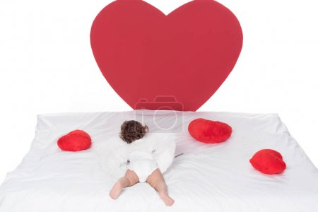 little cupid with wings lying on bed with hearts, isolated on white