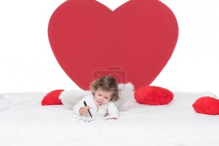 little cherub with wings lying on bed, isolated on white