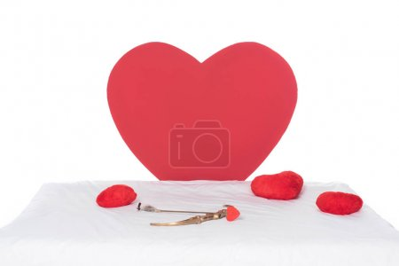heart pillows, wings, bow and arrow on white bed