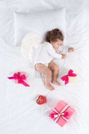 little cherub with wings lying on bed with presents