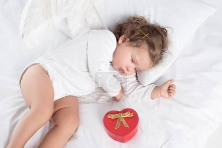 little cherub with wings lying on bed with gift box