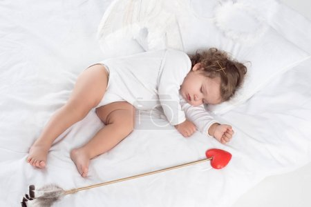 little cupid with wings sleeping on bed with arrow