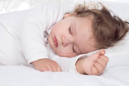 little adorable baby girl sleeping on bed