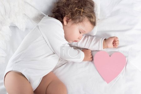 top view of little cherub with wings lying on bed with heart