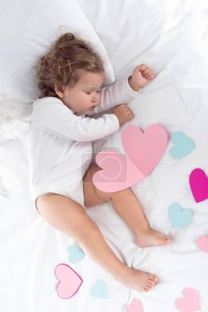 top view of little baby lying on bed with hearts