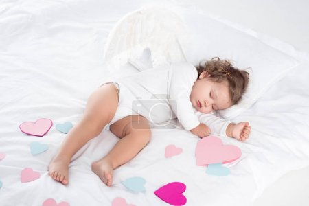 little cherub with wings sleeping on bed with hearts