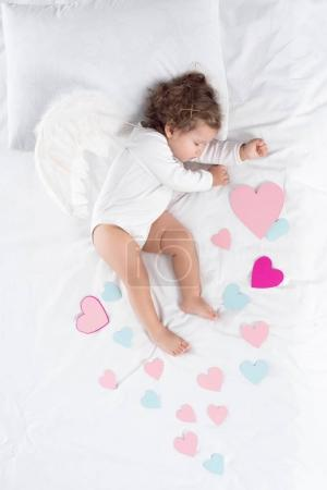 cupid with wings sleeping on bed with hearts