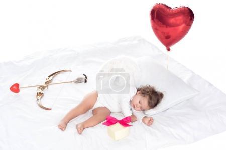 Photo pour Petit ange avec ailes allongé sur le lit, ballon coeur, présent, ARC et flèche, isolé sur blanc - image libre de droit