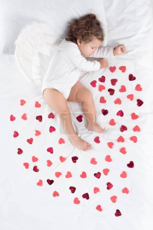 cupid with wings sleeping on bed with red hearts