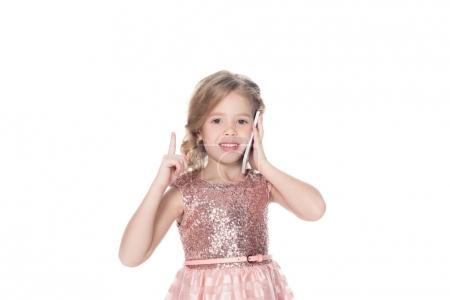 cheerful child pointing up while talking on smartphone, isolated on white