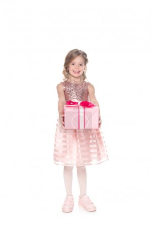 smiling kid in dress with sparkles holding present, isolated on white