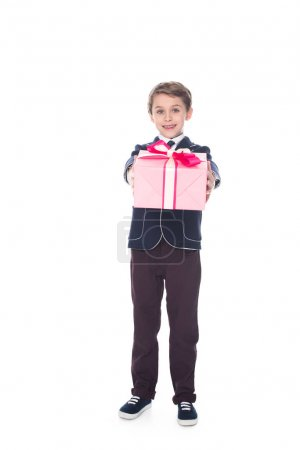 adorable stylish little boy holding gift box and smiling at camera isolated on white