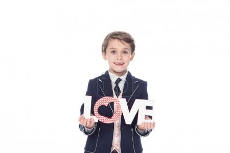 stylish little boy holding word love and smiling at camera isolated on white