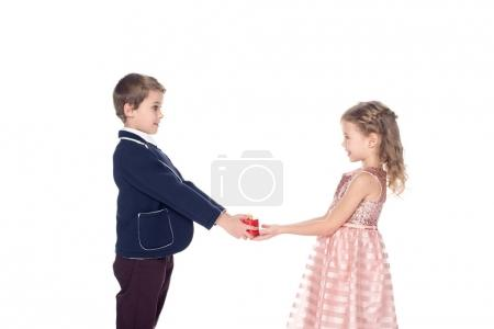 side view of adorable stylish kids holding heart shaped gift box isolated on white