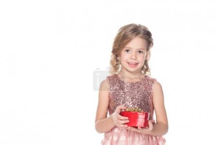 cute kid in pink dress holding heart shaped gift box and smiling at camera isolated on white