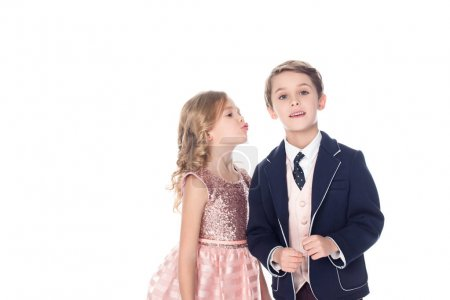 beautiful little girl able to kiss boy in suit looking at camera isolated on white